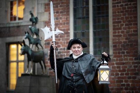 Zu sehen ist ein Mann verkleidet als Nachtwächter. In seiner rechten Hand hält er eine leuchtende Lampe, in der Linken eine Lanze.