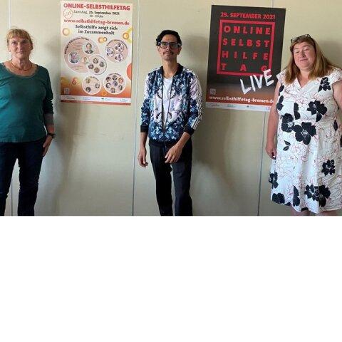 Netzwerk-Geschäftsführerin Sabine Bütow, Talkrunden-Teilnehmer Christian Leon und Sozialsenatorin Anja Stahmann stellen die beiden Plakate zum 18. SelbsthilfeTag während einer Pressekonferenz vor.