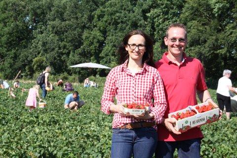 Man sieht Bea und Hajo Kaemena auf ihrem Erdbeerfeld. Beide halten ein Korb mit Erdbeeren