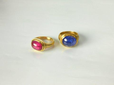 Zwei große Goldringe mit Steinen. Ein Ring hat einen pinken Stein und der andere einen blauen Stein.