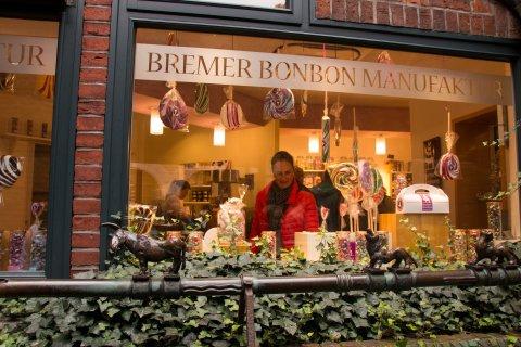 Ein Foto von Außen in das Fenster der Bonbon Manufaktur Böttcherstraße. Leckere Bonbons und große Lollis sind in allen Farben zu sehen.