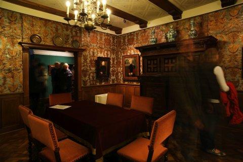 Besucher stehen in einem Ausstellungsraum und schauen sich Gemälde an.