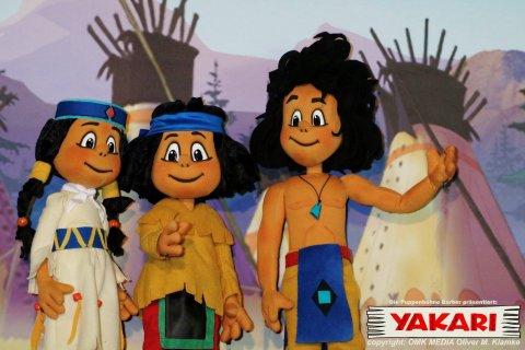 Drei Puppen des Stückes Yakari steht vor einer Wand mit Zelten.
