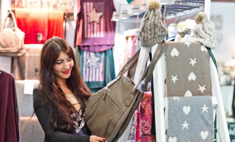 Eine Frau bewundert eine Tasche am Stand eines Ausstellers.