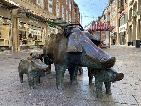 Schweine aus Messing stehen in einer Einkaufstraße. Dem größten Schwein wurden Kopfhörer aufgesetzt.