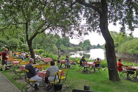 Menschen sitzen draußen an Tischen an einem Fluss im Grünen.