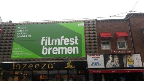 """Außenfassade des Kinos """"Schauburg"""" an der ein grüner Banner zum Filmfest hängt."""