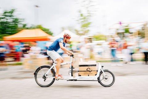 Mann fährt mit dem Lastenrad