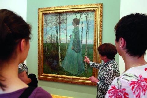 Museumbesucherinnen schauen auf ein Gemälde. Davor steht eine Frau die etwas zu dem Bild erklärt.
