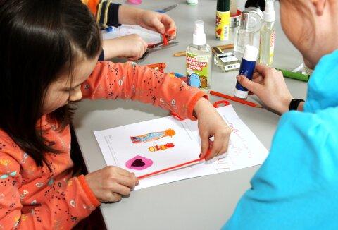Kinder sitzen an einem Tisch und basteln und malen.