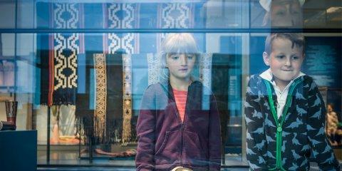 Zwei Kinder betrachten etwas durch eine Glasscheibe in einem Museum mit bunt gemusterten Teppichen und Exponaten