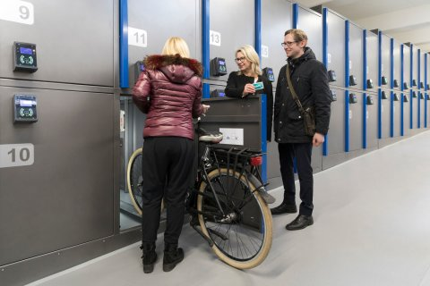 Eine Frau schiebt gerade ihr Fahrrad in eine der Fahrradboxen in dem Fahrradparkhaus am Dom.