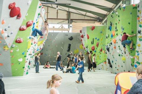Zu sehen ist eine Kletterhalle. Rechts und links stehen Kletterwände, an denen Menschen klettern. In der Mitte der Wände ist eine Matte ausgelegt, auf der Menschen sitzen und laufen.