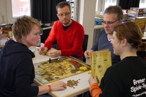 Vier Personen sitzen an einem Tisch und spielen ein Brettspiel