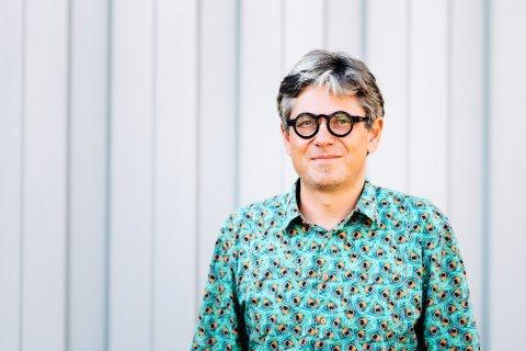 Ein Mann mit schwarzumrandeter Brille schaut in die Kamera, im Hintergrund eine graue Wand; Quelle: WFB/Jonas Ginter