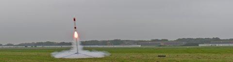 Eine rot-weiß gestreifte Rakete startet.