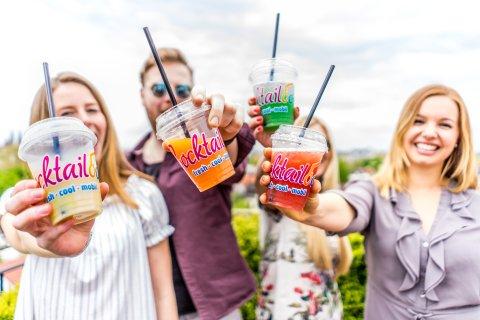 Einige junge Leute halten ihre bunten Cocktails in die Kamera.
