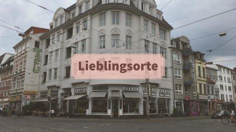 Ein braunes Schild mit Schriftzug. Im Hintergrund ist ein weißes Haus an einer Kreuzung zu sehen.