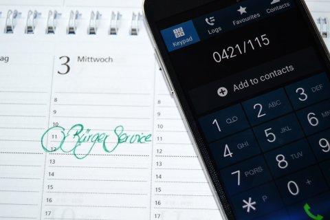 Ein Handy wählt die Nummer des Bürgertelefons