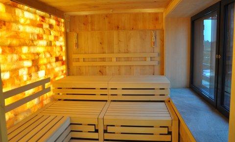 Eine leere Sauna von innen mit einer beleuchteten Wand aus Steinen.