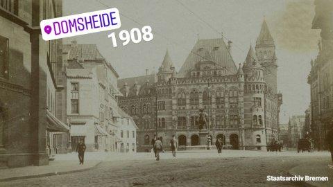 """Zu sehen ist ein kleiner Platz mit einer Statue. Am Ende des Platzes steht ein großes Gebäude mit mehreren kleinen Türmen. Links im Bild ist eine angeschnittene Häuserreihe zu sehen. Ein lilafarbener Schriftzug mit der Aufschrift """"Domsheide"""" sowie die weiße Zahl """"1908"""" sind auf das braune Bild gelegt."""