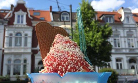 Ein Spaghetti Eis mit einer Waffel in einem blauen Becher wird in der Wachmannstraße bei Eis Molin hochgehoben.