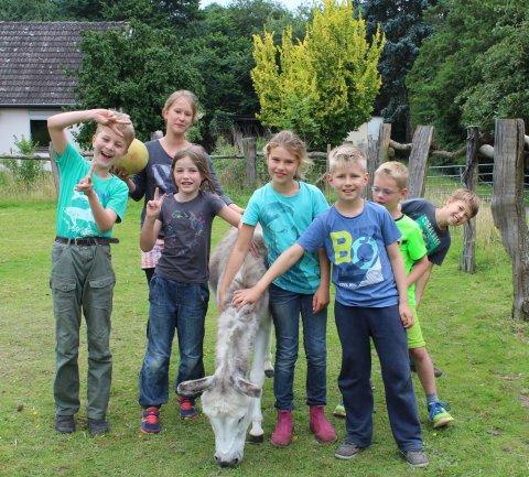 Kinder lächeln in die Kamera. In ihrer Mitte steht ein Esel, den einige von ihnen streicheln.