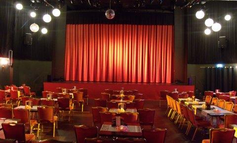 Der leere Theatersaal in schönem Licht und vor dem großen roten Vorhang.