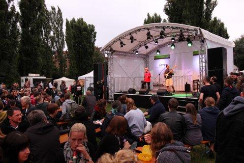 Die sogenannte Kulturbühne auf dem Fährmannsfest. Davor das Publikum auf Bierbänken. Auf der Bühne sind zwei Musiker mit Gitarre.