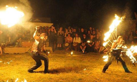 Zwei Männer bieten abends eine Feuershow.