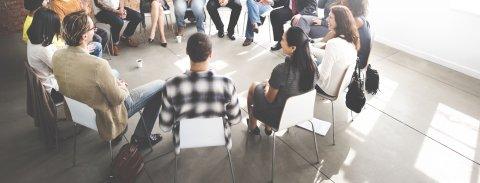 Ein Stuhlkreis von Menschen, die zusammensitzen.