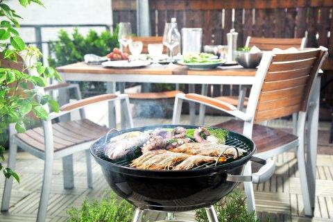 Im Vordergrund ein mit verschiedenen Lebensmitteln bestückter Grill, im Hintergrund ein gedeckter Tisch mit vier Stühlen.