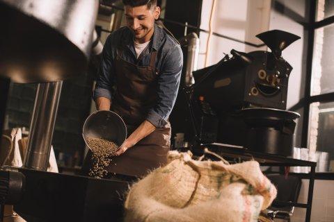 Ein Arbeiter schüttet Kaffeebohnen in eine Maschine