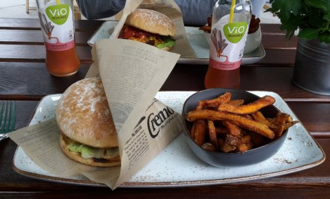 Zwei Menus mit Burgern, Süßkartoffelpommes und Rhabarberschorle auf dunklem Holztisch.