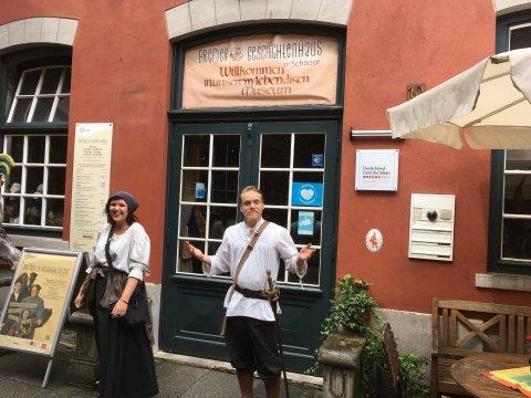 Zwei Darsteller stehen in ihren Kostümen vor dem Geschichtenhaus im Schnoor.