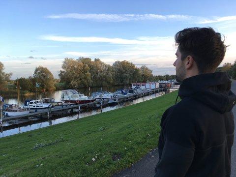 Eine Person ist rechts im Bild seitlich zu sehen, steht auf einem Deich und blickt auf einen Steg, an dem Boote festgemacht sind.