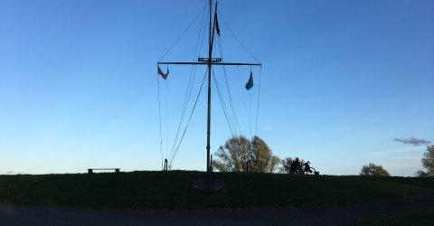 Ein Bauwerk, das an die Segel eines Bootes erinnert, vor blauem Himmel und auf einem Deich