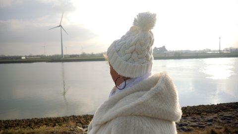 Zu sehen ist eine Person von hinten, die eine weiße Jacke und eine weiße Mütze trägt und am Ufer steht. Von dort aus sieht man das Wasser der Weser und das gegenüberliegende Ufer, auf dem Häuser und Windräder stehen.