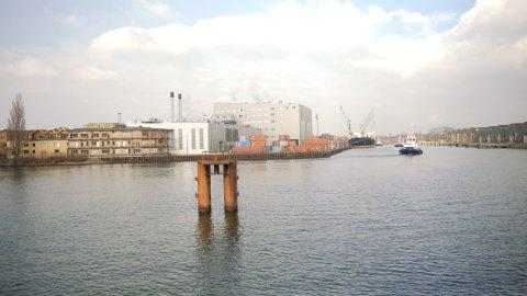 Zu sehen ist das Wasser der Weser. Auf der gegenüberliegenden Seite befinden sich Gebäude in Ufernähe. Rechts legt ein Schiff an, drei kleinere Boote liegen in der Nähe des Schiffs auf dem Wasser.