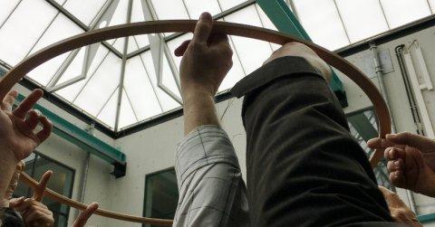 Ein großer Holzring von von vielen Zeigefingern in die Höhe gehalten
