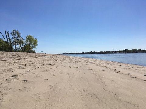 Zu sehen ist ein langer, weißer Sandstrand, an dessen rechter Seite blaues Wasser grenzt. Links vom Strand stehen grüne Bäume. Der Himmel ist strahlend blau.