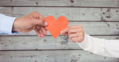 Zwei Hände halten ein rotes Herz vor einer Holzwand