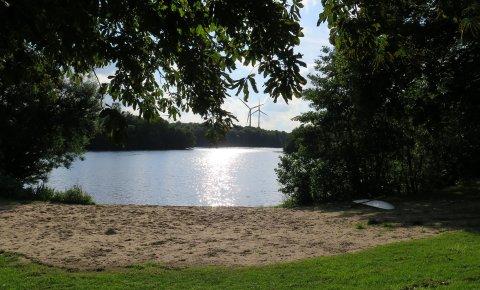Eine Foto vom Ufer auf den Mahndorfer See. Das Sandufer und das grüne Ufer liegen im Vordergrund. Im Hintergrund sind moderne Windräder zu sehen.