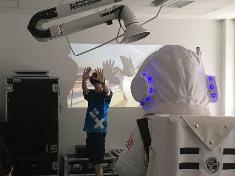 Astronaut steht vor einem Studenten, der eine VR-Brille trägt