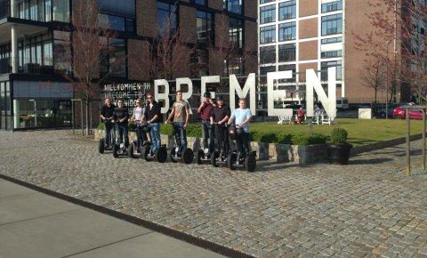 Eine Gruppe von acht Männern auf Segways, vor dem Bremen-Schriftzug in der Überseestadt.
