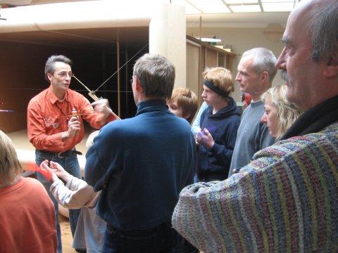 Ein Mann steht vor mehreren Mensch und zeigt auf das Holzmodell in seiner Hand. Im Hintergrund befindet sich ein Windkanal.
