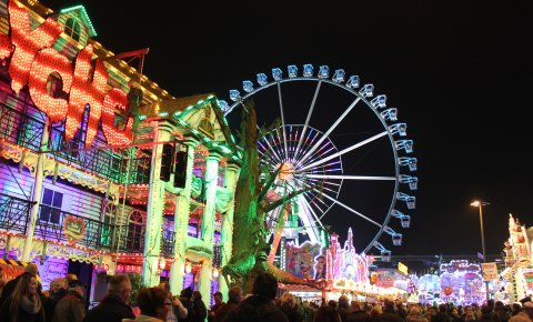 Bunt beleuchtete Buden und Fahrgeschäfte auf dem Bremer Freimarkt bei Nacht.