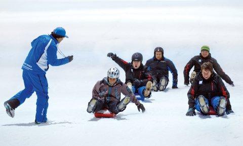 Fünf Personen rodeln im Schnee um die Wette, eine sechste nimmt die Zeit.