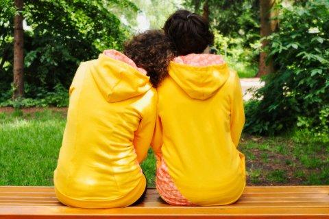 Zwei Personen sitzen aneinander gelehnt in gelber Kleidung vor grüner Kulisse.
