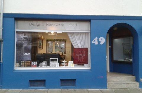 Der Eingang zu KOMOOD blaue Hausfassade
